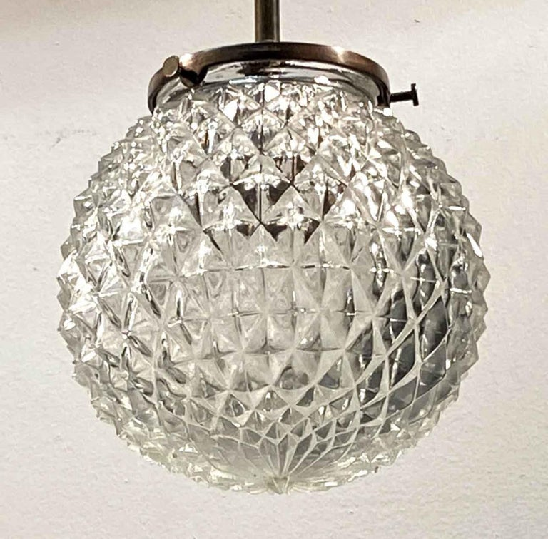 1990s Mid-Century Modern style textured cast glass globe configured on a new brass pole fitter. This can be seen at our 400 Gilligan St location in Scranton. PA.