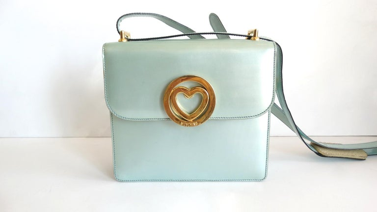 Be The Ultimate 90s Girls With This Moschino Shoulder Bag! Features baby blue patent leather and gold hardware. Outer front face includes a signed Moschino heart pendent snap closure and a long adjustable belt style strap. Interior is fully lined