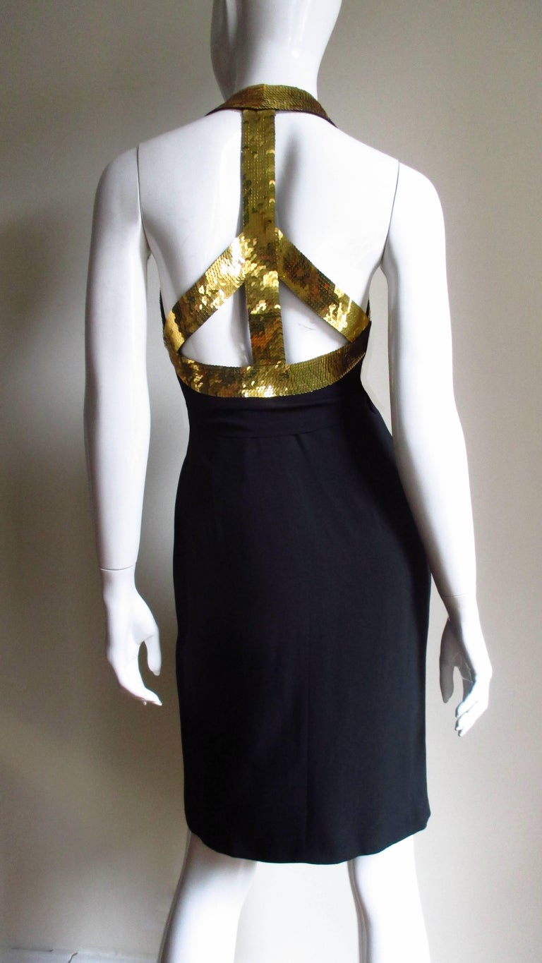 A fabulous Peace Sign black dress from Moschino Couture.   It is a wrap style dress which ties at the waist.  Gold sequin detail along back of neck and underarms in the front continue to the back and form the circle portion of a Peace Sign all in