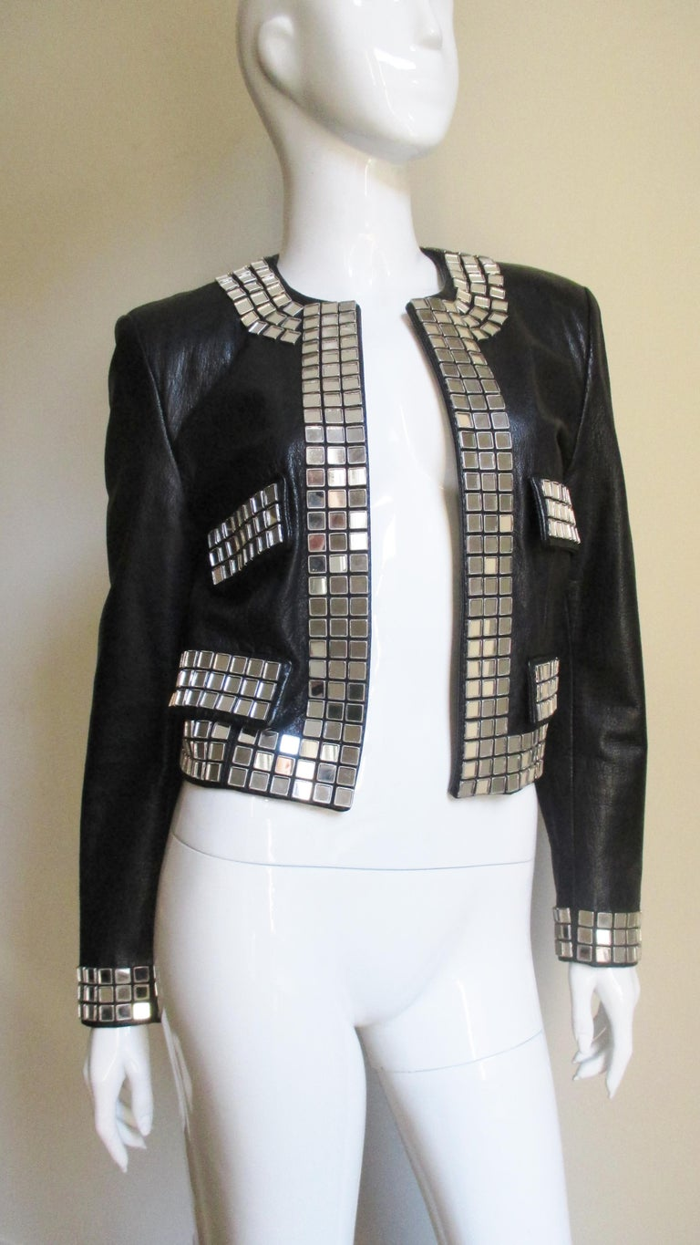 A fabulous black leather jacket from Moschino.  It is open in front with the pocket flaps, cuffs and jacket edges outlined in 3 rows of small square mirrors. It is fully lined and has lightly padded shoulders.   Fits sizes Small, Medium,  Bust
