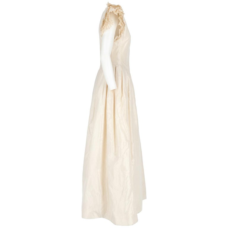 The romantic Nina Ricci Paris ivory silk long wedding dress features a long bell flared skirt with v-neck and pleated short-sleeves, shoulder paddings and back zip fastening.  Size: 44 IT Made in France  Linear measures  Height: 151 cm Bust: 40