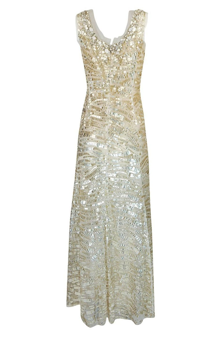 This wonderful Oscar de la Renta gown is red carpet worthy and would even be a potential wedding dress for the bride looking for a non-traditional choice. It is in immaculate condition and is covered with a dense application of muted gold  sequins