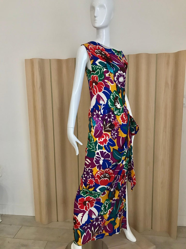 Vintage  Oscar De La RENTA Vibrant multi color floral print dress in purple, green , turquoise, orange, blue and magenta silk print dress with sequins and bow.  Dress has side slit with bow.  Size: Medium Bust: 36 inches/ Waist: 30 inches/ Dress