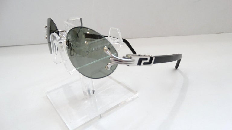 The Perfect Shades For The Summer Sun! Circa 1990s, these dead stock Porta Romana oval sunglasses feature a semi clear black lens and silver hardware. The silver hardware sits on the lens, (faint crack lines by screws) features subtle line work