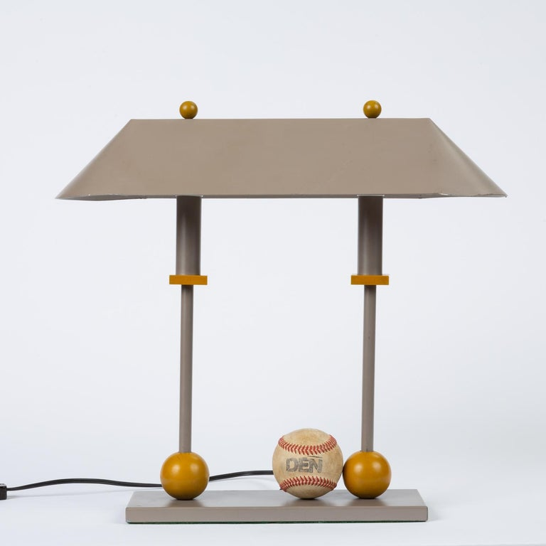 A Postmodern iteration of the Classic two-pillar banker's lamp from lighting designer Robert Sonneman for George Kovacs. Designed in 1990, this piece has a triangular shade in putty-gray enameled aluminum, supported by two columns on a flat base.