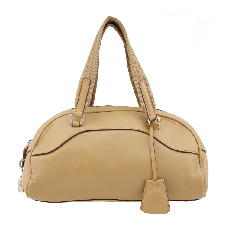 Prada's iconic 1990's bowling bag. Beige leather with silver tone metal hardware. Monochromatic beige top stitching. Features silver lock and key. Chevron textured fabric top handle. Made in Italy. Excellent vintage condition - clean interior.