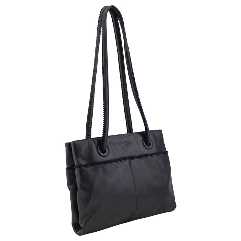 Prada bag from the early 1990s. Black leather fold over style with navy blue grosgrain and macramé trim. Navy blue top stitching. Large Prada blind stamp on front. Interior is two pockets. Long shoulder straps. Black lining with all over Prada logos