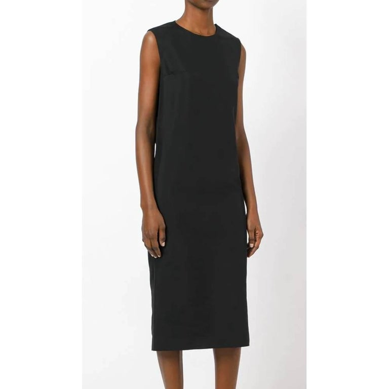 Prada black dress in black silk and cotton blend, round neck model, central slit on the back and without sleeves. Medium-long length. Years: 90s  Made in Italy  Size: 42 IT   Linear measures  Lenght: 116 cm Bust: 43 cm  Waist: 43 cm  Hip: 48