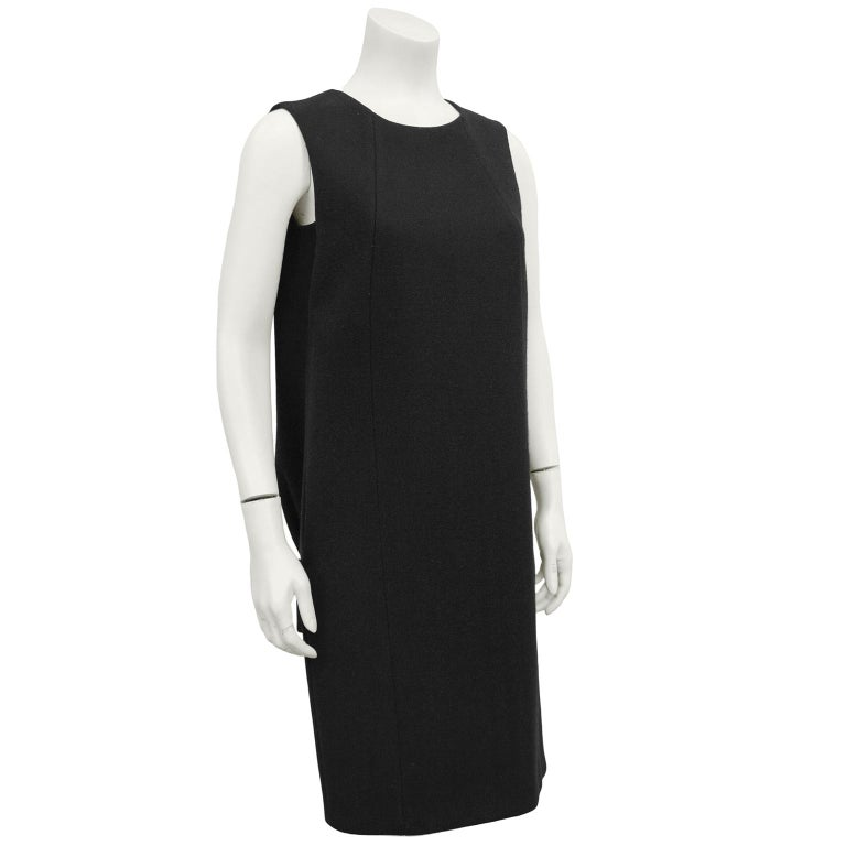 Stunning 1990s Prada black wool dress. Simple sleeveless from the front with two side seams. Back features a large inverted box pleat down the centre back with a wide drop waist half belt. Inspiration by early letter shaped Balenciaga silhouette.