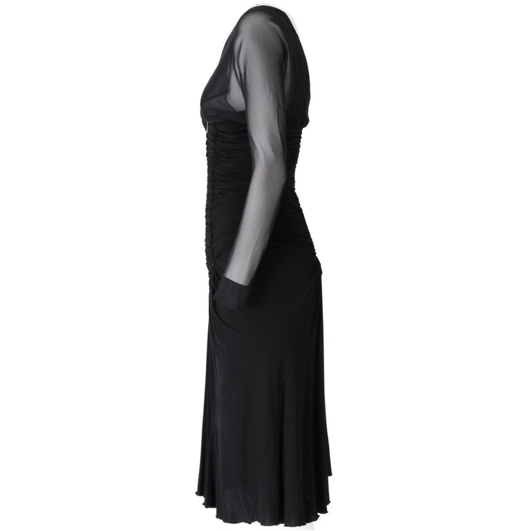 Roberto Cavalli V-neck black dress, long semi-transparent sleeves with semi-opaque inner lining, empire cut with decorative curls at abdomen height and wide skirt below the knee, zip closure on the back.  The item shows slight signs of wear on the