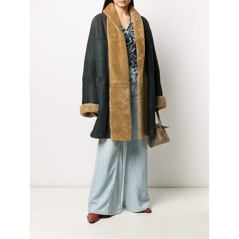Romeo Gigli greyish dark blue sheepskin coat with beige fur. Featuring a front buttoning, long sleeves, two front pockets and central rear vent.  This item shows some signs of wear on the leather, as shown in the pictures.  Years: 90s  Made in
