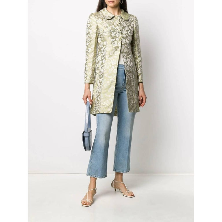 Romeo Gigli slightly iridescent pastel green silk with jacquard pattern jacket. Peter Pan collar and three front covered buttons. Center back vent and snug fit.  The product has a missing button in the right cuff as shown in the pictures.  This item