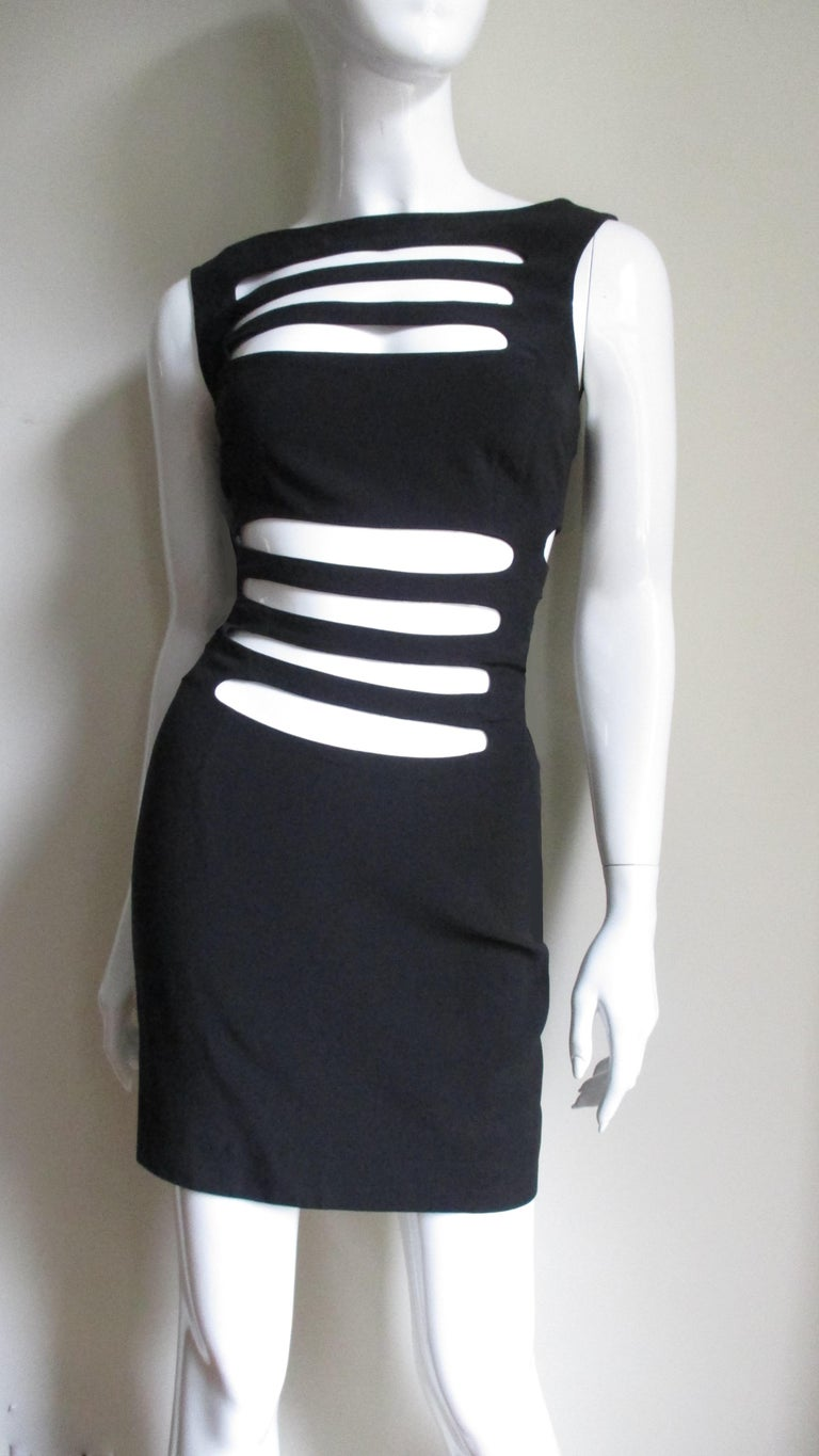 A fabulous black dress from French designer Sophie Sitbon.  It is a simple sleeveless crew neck dress covered in long horizontal cut outs across the midriff, upper chest and sides.  The back has a scoop neckline.  It is unlined and has a center back