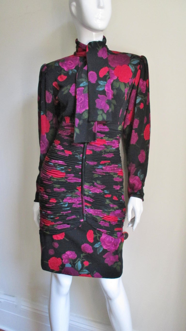 A very pretty fine wool jersey fitted dress from Emanuel Ungaro with purple and red flowers popping against the black background. It has a tie neckline, full sleeves with zipper cuffs and beautifully intricate horizontal ruching around the dress