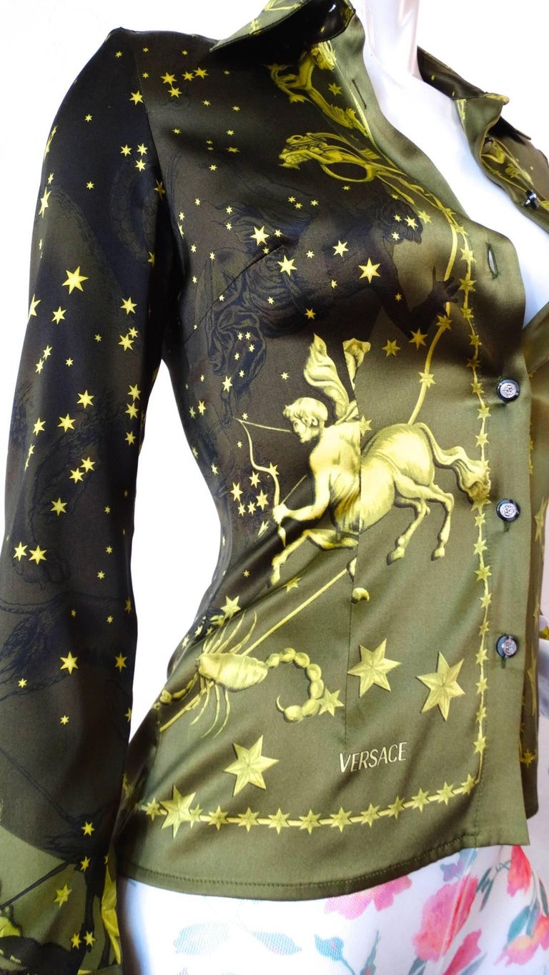 This amazing 1990s Versace constellation themed blouse will have you seeing stars! Incredible olive green ombre silk with golden constellation inspired print- featuring cherubs, stars, and the astrological sign motifs. Buttons up the front with