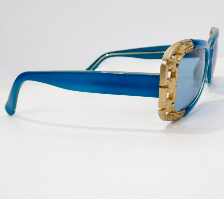 Never Go Unnoticed With These Electric Blue Versace Sunnies! Circa 1990s, these beautiful blue rounded rectangular sunglasses are a dead stock treasure and feature contrasting gold plated chain link metal accents as the outside trim. The perfect