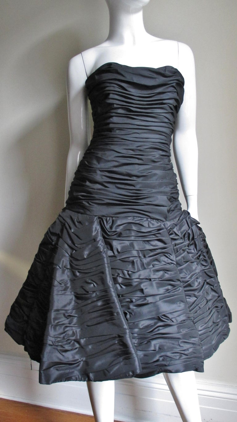 A beautiful black taffeta dress from Victor Costa.  It has a strapless sweetheart neckline with a horizontally ruched drop waist bodice with vertical boning for support. The skirt is ruched, sculptural and full.  The dress has a back zipper and is