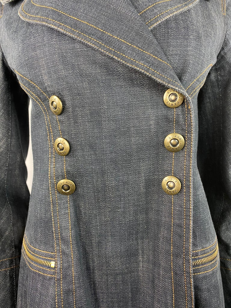 Product details: Circa 1990's Size medium Featuring 100% cotton dark blue denim, mid length coat with gold tone hardware, front click in buttons closure, dial zip pockets. Made in France.