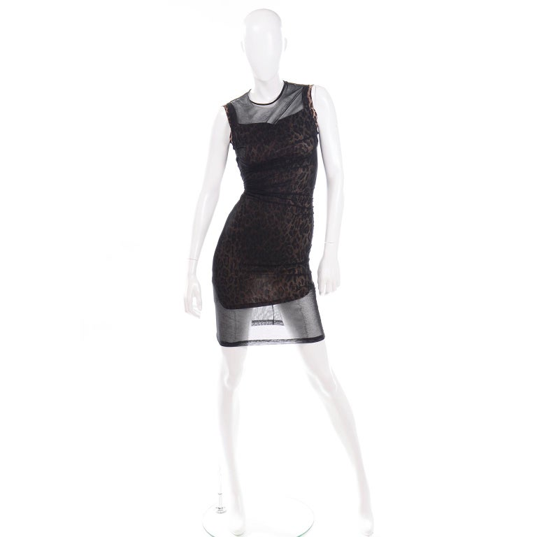This dramatic vintage 1990's Dolce & Gabbana bodycon mini dress has a  tight fitting stretch leopard print under dress with a unique sheer black overlay.  The wonderful leopard under dress is shorter than the overlay and has a round neckline with