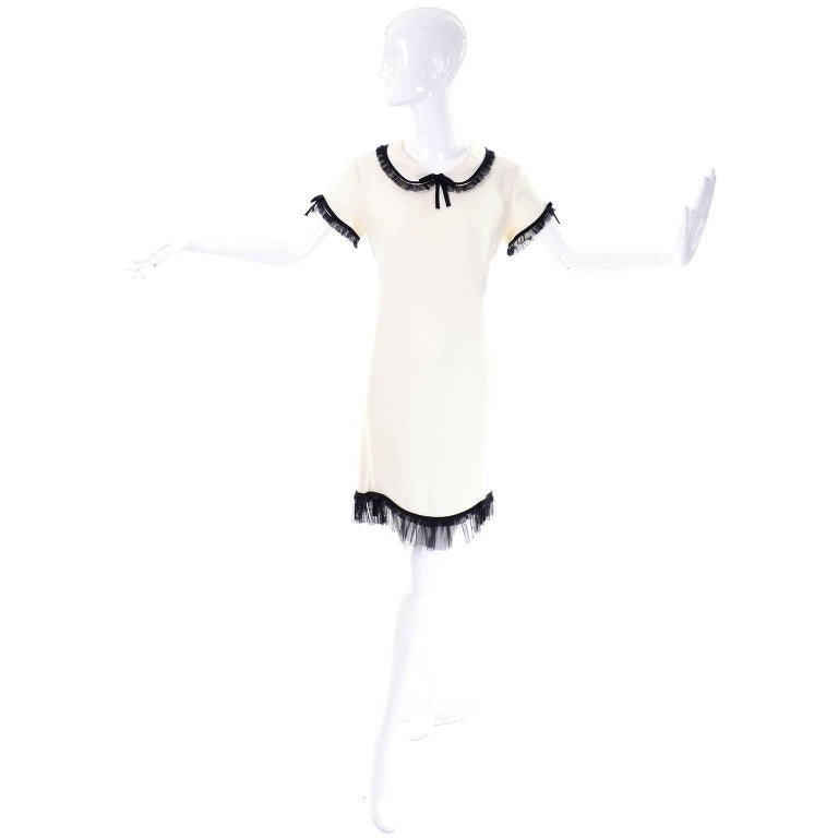 This adorable vintage short sleeved dress from Moschino is made in an ivory rayon / acetate blend crepe and has black ruffled netting or tulle at the collar, hemline, and sleeves.  This Cheap and Chic by Moschino dress was made in Italy,  The dress