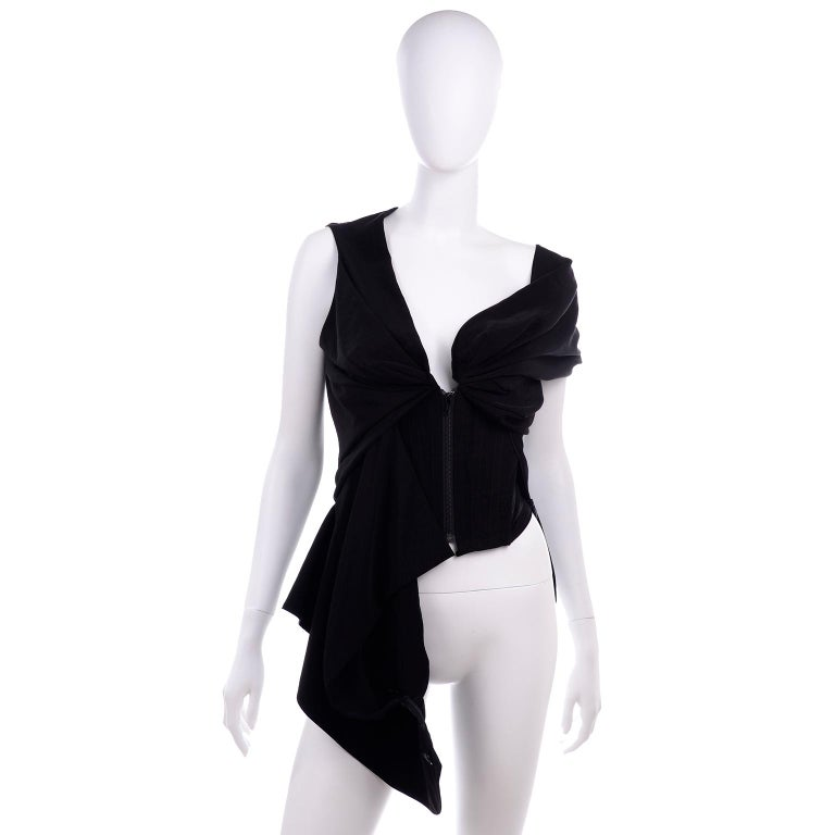 We love Vivienne Westwood pieces and this is an amazing top. This red label black top has a metal zipper down the center front and mesh panels on each side of the corset with an elastic back.The top can be worn in a couple of different ways and we