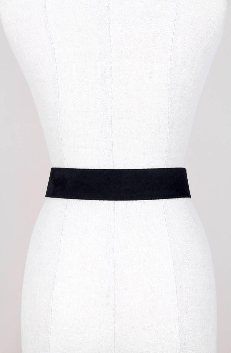 Classic 1990s Yves Saint Laurent YSL curved style black suede belt featuring a suede covered buckle with gold tone accents and a gold tone logo at the end of the belt. It is lined in black leather and stamped inside
