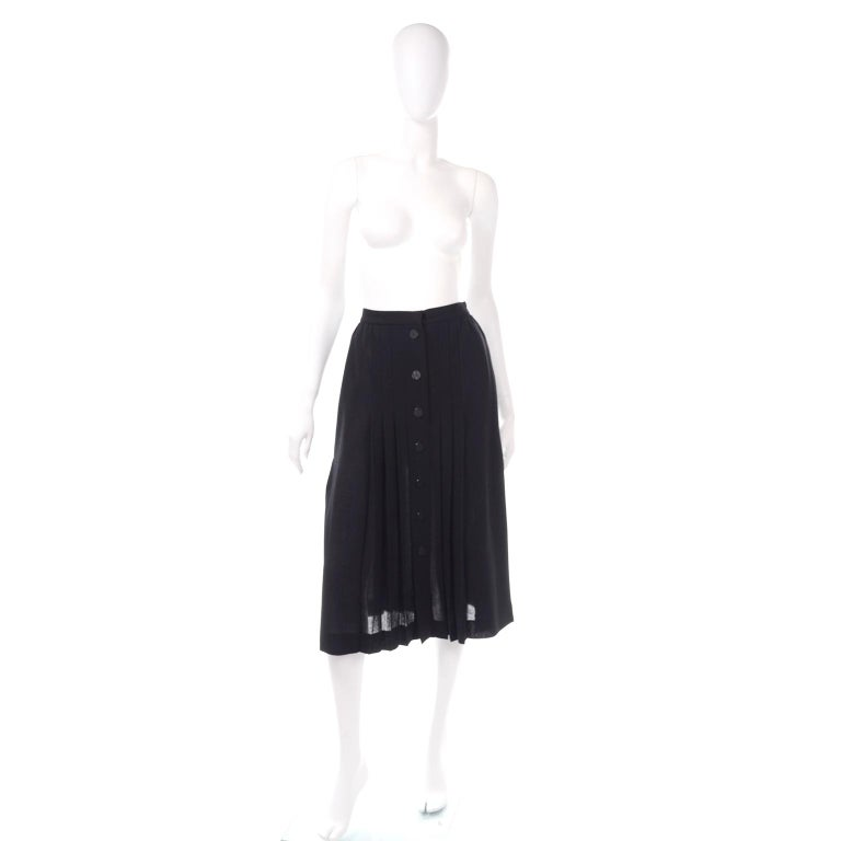 This is such a sleek YSL vintage midi skirt from the 1990's. The fabric is a luxe  lightweight black wool crepe, and there are knife pleats that start just below the hips. The skirt buttons down the front with textured black buttons and a hook and