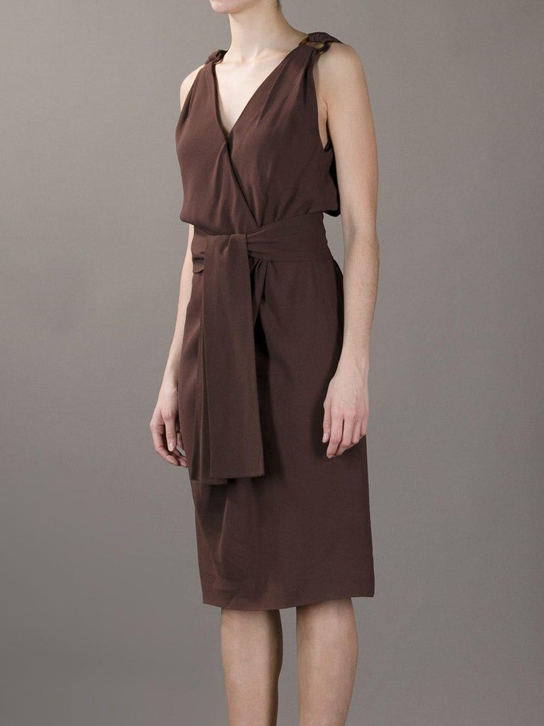 Lovely Yves Saint Laurent brown viscose dress from 90s collection. The dress features an elegant deep v-neck and draped detail on the bust. The deep back neckline is embellished by two animalier decorative buckles and the waist is wrapped by a brown