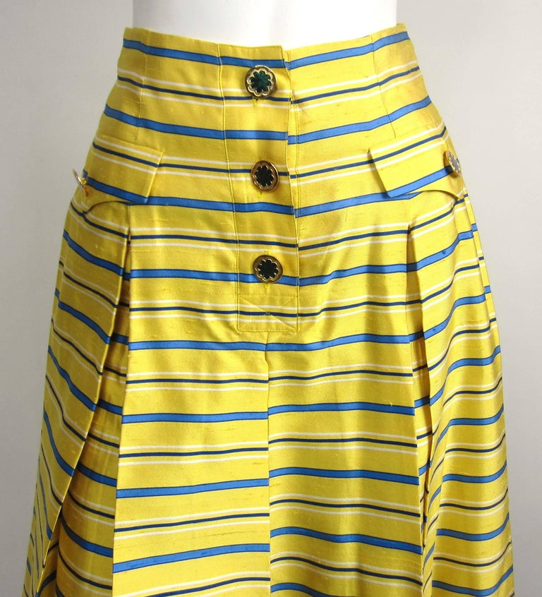 Stunning Yellow and blue striped YSL skirt with gold-tone buttons. The extra button still attached inside the skirt. I have the blouse that matches this skirt on our storefront. Labeled a size 34  Will fit a size small, please check measurements.