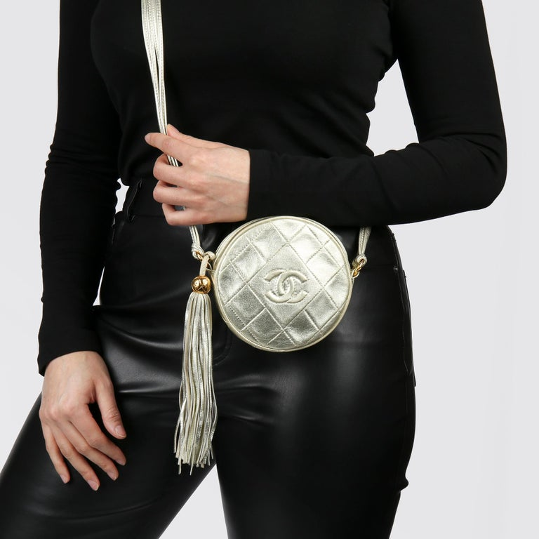 CHANEL  Champagne Gold Lambskin Vintage Timeless Round Fringe Pochette  Xupes Reference: HB3776 Serial Number: 1988588 Age (Circa): 1991 Accompanied By: Chanel Box, Dust Bag, Authenticity Card Authenticity Details: Authenticity Card, Serial Sticker
