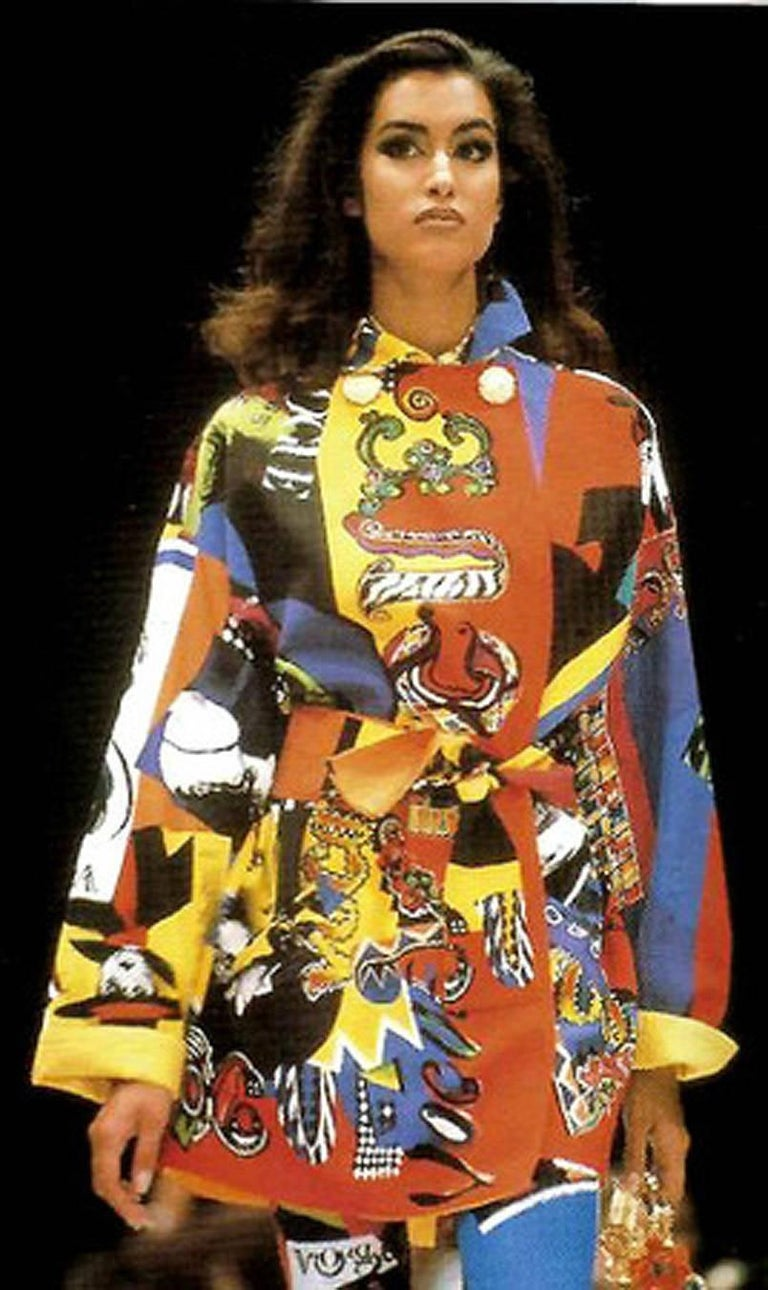 Iconic Gianni Versace Couture colorful novelty Vogue print trench jacket from his documented 1991 runway spring/summer collection. The first Versace boutique was opened in 1978 and its popularity was immediate. Today, Versace is one of the world's
