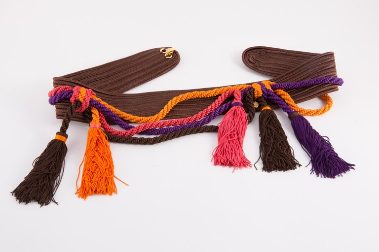 Multicolor Yves Saint Laurent braided belt featuring brown braided belt, and purple & orange fringed pompons, logo gold tone metallic plaque. See catwalk 1991s photo. In excellent vintage condition. Made in France.  Maxi Length 31.4in. (80cm) Width