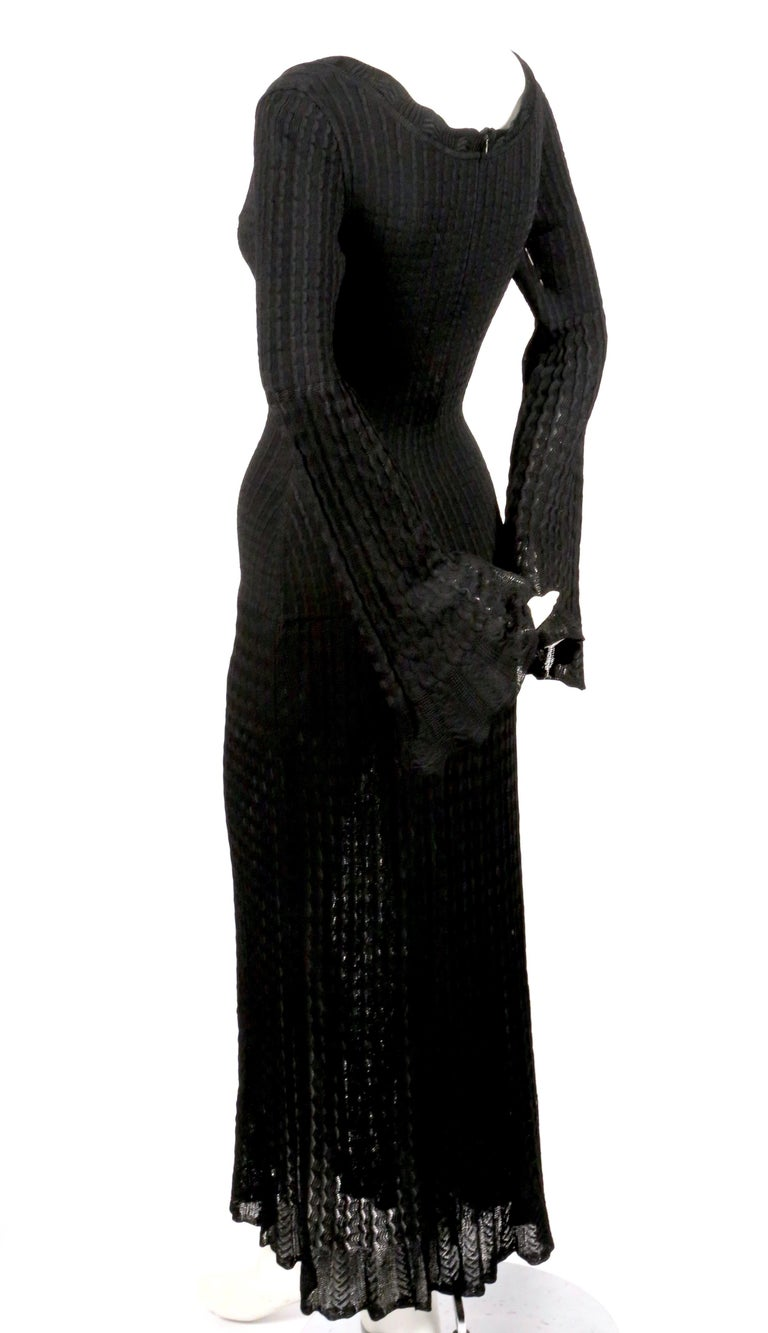Jet-black, open knit dress with flounce hemline and bell sleeves from Azzedine Alaia dating to 1992. Size is unmarked however this best fits a size 'S'. Approximate measurements (unstretched): shoulder 15