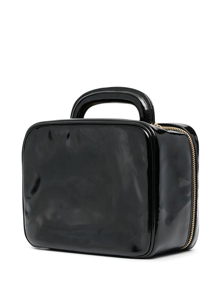 Black patent Timeless Vanity bag from Chanel Pre-Owned featuring gold-tone hardware, a top logo zip closure, a top handle, a front logo detail, a detachable shoulder handle, inside velvet compartments, inside pockets, inside logo zip pocket. Circa