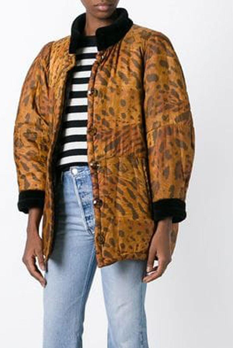 1996s Yves Saint Laurent brown silk animal print padded coat featuring a front button fastening, side pockets, long sleeves, a short length, a straight hem and a black velvet collar and cuffs. See catwalk image. 100% silk In excellent vintage