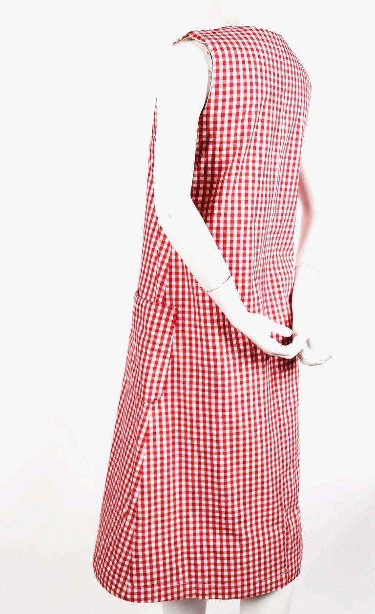 Red gingham cotton dress with padding at shoulders and hem from Comme Des Garcons dating to the 1997 'Body meets dress, dress meets body' collection often referred to as the Lumps and Bumps collection. Size 'S'. Approximate measurements: bust 35