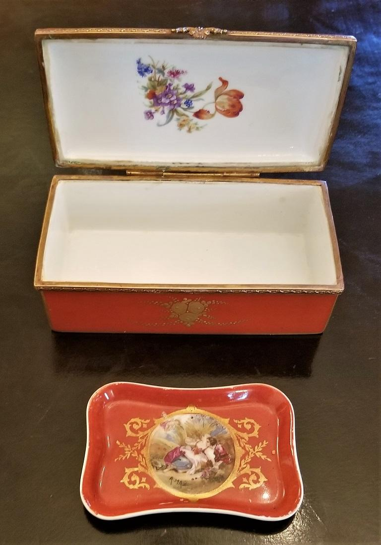 Presenting a gorgeous and rare matching pair, namely, a 19th century Sevres Porcelain trinket box with ring tray.  The trinket box os a very good size and has gilt edging and overlay throughout.  The central hand painted medallion on the lid is