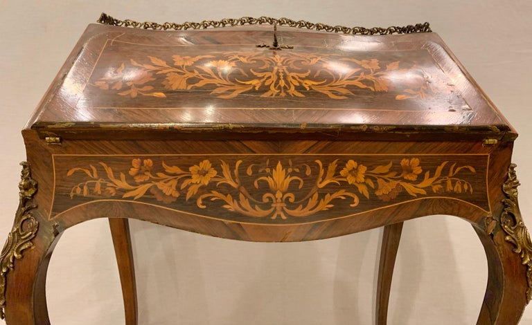 19th-20th century Louis XV style bombe French marquetry inlaid desk. Having bronze mounts. Having three drawers and a slant down top. The writing surface with a leather top.