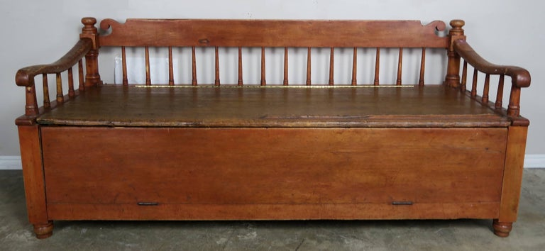 19th century American painted storage bench with upholstered down filled loose cushion. Spindle back and sides. Measures: Seat height 25