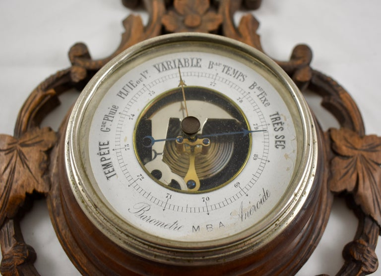 From Switzerland, a black forest wall barometer and thermometer set into a walnut frame, hand carved in a scrolled floral pattern, circa 1890-1900.