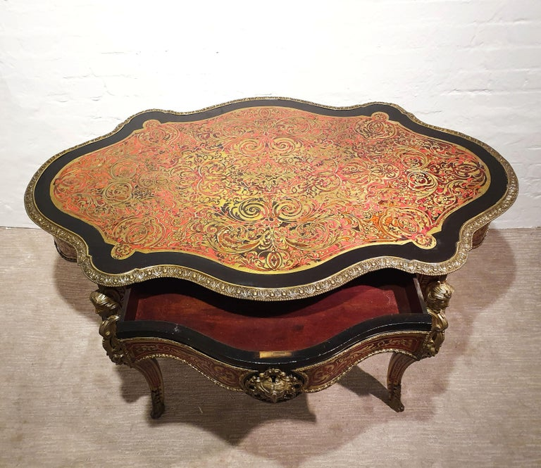 This magnificent and intricately detailed 19th century Boulle shaped center table features one central top drawer with a shaped skirt and ornate masks on each side, surrounded by an ebonised wood border around the top edge. The table is supported on