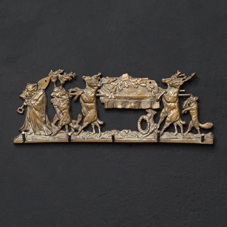 Very 19th century satirical hunting depiction on a wall wardrobe in heavy cast brass relief. 
