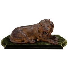 19th Century Carved Wooden Reclining Lion on a Green Velvet Base