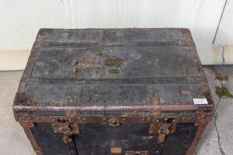This antique French trunk dates to the 1850s. It's primarily black with iron details and the body is canvas. There are leather handles on each side and a patinated monogrammed brass plate on the lid. The ovular plate reads