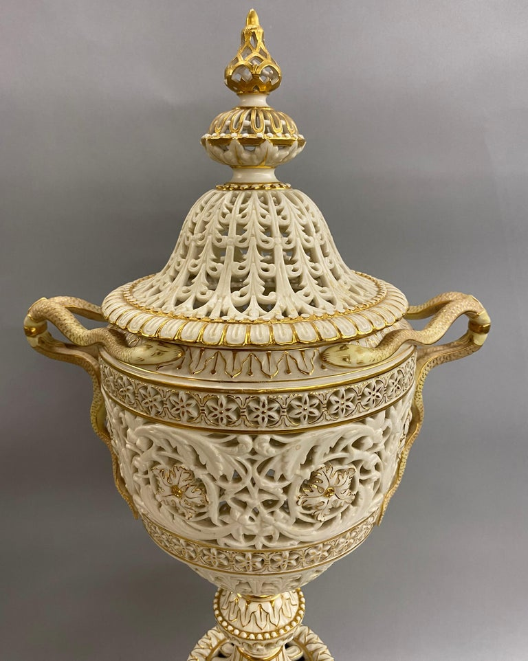 An exceptional large English gilt ivory porcelain reticulated covered urn or centerpiece with finely detailed serpent handles on an out-swept scroll footed base, with the Grainger & Co Royal China Works Worcester England hallmark under both the lid