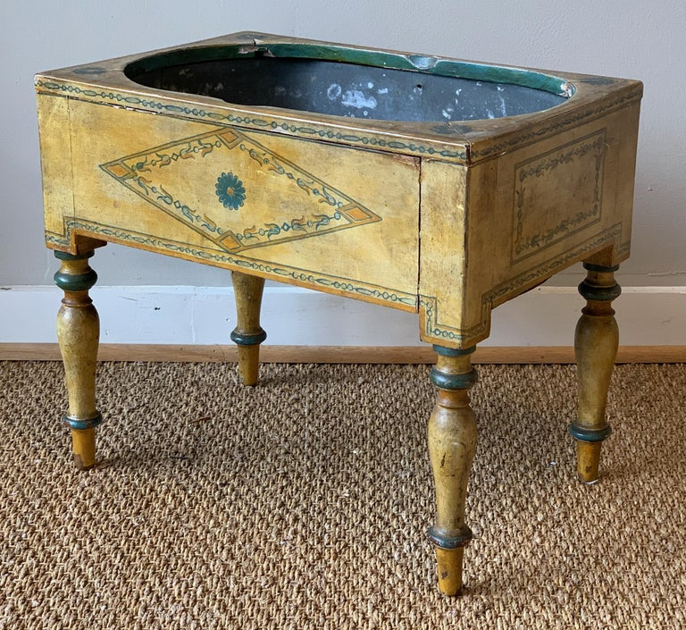 A small and charming early 19th century English paint decorated zinc lined planter. The entire surface in a muted mustard yellow with subtle green and gold accents.