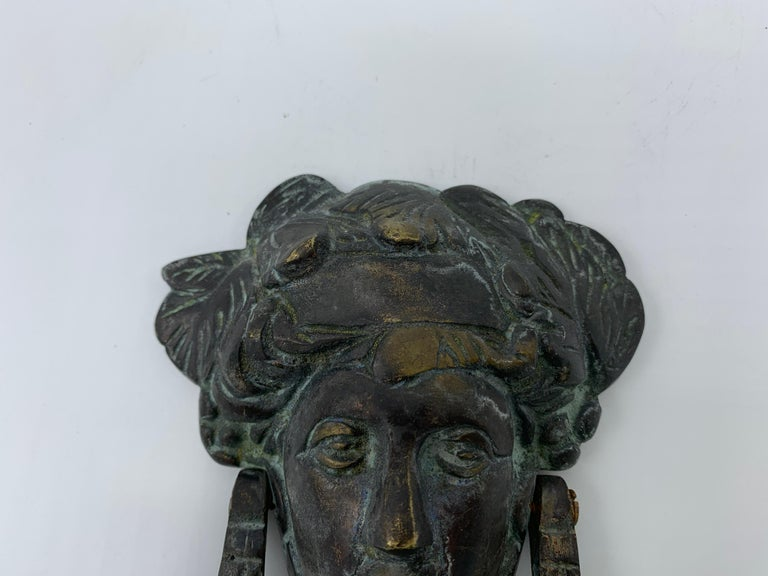 Listed is a stunning, 19th century. French bronze door knocker with a dark verdigris finish. The pieces focal point is of a Victorian woman's face, possibly a goddess. Please note, this piece is a rare find, with its plaque at the centre of the