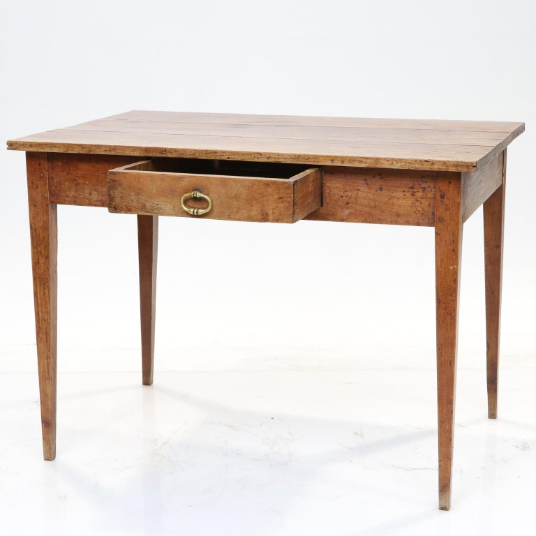 19th century French country side table  This table is made of cherry wood, the top individual cut planks on the top, with a luxurious patina. Simple tapered legs. There is one functional drawer. Pegged construction noticeable on the legs.