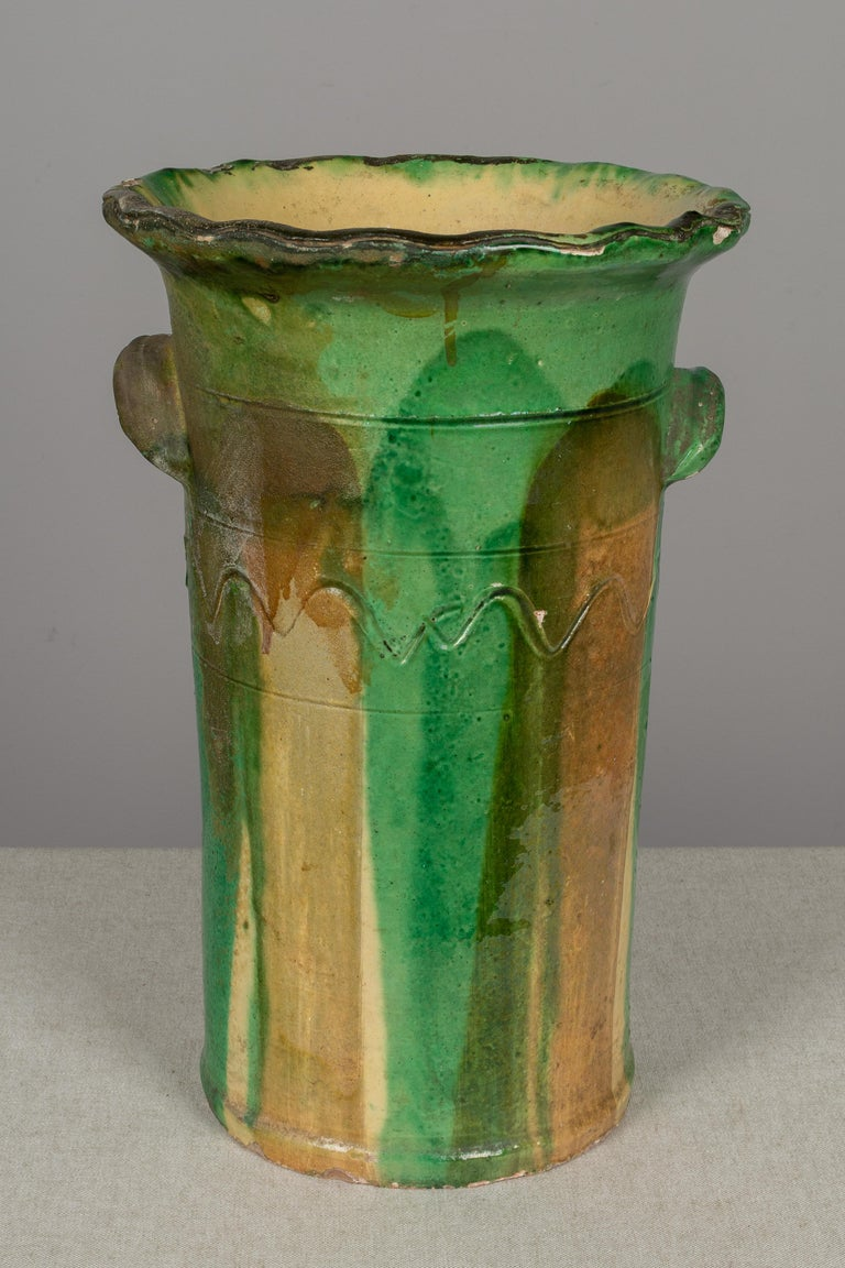 A 19th century earthenware pottery vase or vessel from the Southwest of France having a beautiful green glaze with streaks of ochre and yellow. Tall, slightly tapered shape with a diameter of 7.5