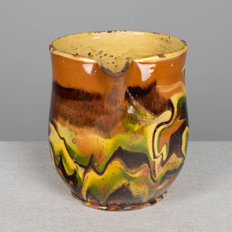 A 19th century French glazed terracotta pottery Jaspe pitcher from the Savoie region with colorful marbleized pattern of orange, green and yellow. Restored hairline crack. Please refer to photos for more details. We have a large selection of French